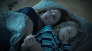 Karppi (Pihla Viitala) pitää patjalla nukkuvaa lastaan kainalossaan kyyneleet silmissään.