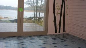 Golv målat som hav och vägg målad med träd som vyn utanför glasdörrarna.