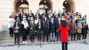 Körsångare i klädda studentmössa sjunger. Kvinna i mörkt hår och röd jacka dirigerar.