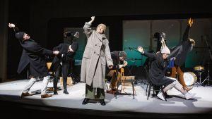 Sex skådespelare i vinterrockar står och sitter på en teaterscen.