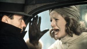 Mies istuu autossa, nainen huutaa ikkunan takana. Kuva elokuvasta Fasisti.