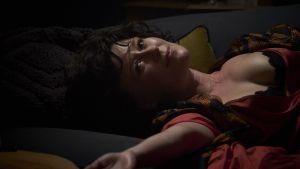 En lättklädd Amanda ligger på en säng och tittar förföriskt in i kameran.