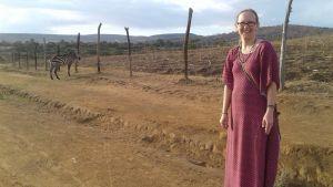 Anna Dahlbacka på en lokal väg, en zebra i bakgrunden.