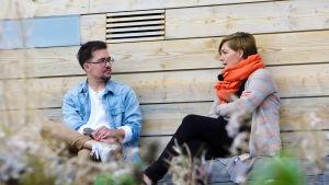 Adam Guarnieri och Maria Sundblom Lindberg i samspråk utomhus framför ljus trävägg på ön Lonnan i Helsingfors.