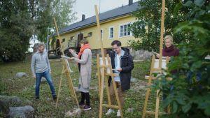 Fyra människor målar tavlor utomhus.