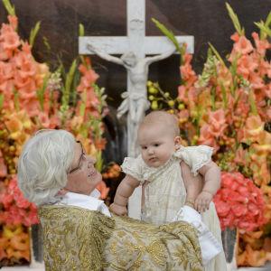 Ärkebiskop Antje Jackelen håller upp den lille prinsen som har fått namnet Alexander Erik Hubertus Bertil