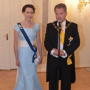 Presidenten och hans maka står festklädda vid en mikrofon