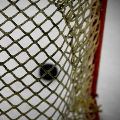 Puck i ishockeymål.