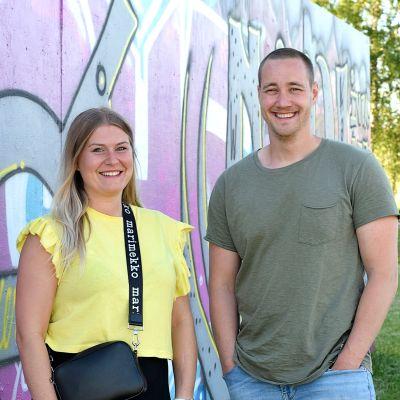 Producent Elin Sundell i gul t-skjorta och fotograf Ian Granström i grönt. De står framför en vägg med grafitti i lila färger.