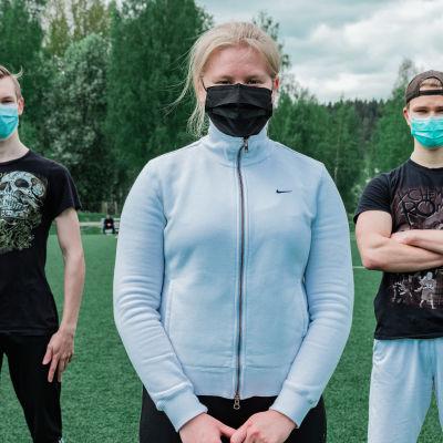 Arto Paananen, Siiri Virtanen ja Ante Ekholm seisovat jalkapallokentän viheriöllä.