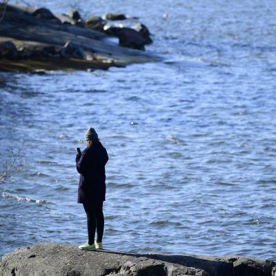 Kvinna på en strand med en mobiltelefon. Helsingfors 4.4.2020