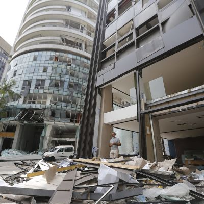 Personer står nära en skadad byggnad efter explosionen i Beirut.