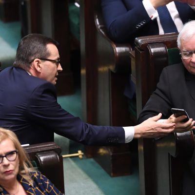 Mateusz Morawiecki näyttää kännykkän näyttöä Jaroslaw Kaczynskille parlamenttisalin käytävän yli