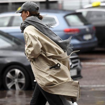 En person i keps, halsduk och trenchjacka går på en gata i blåsigt väder.