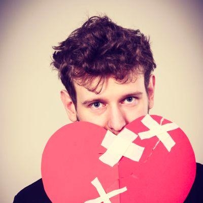 Närbild på en man som håller i ett pappershjärta som är brustet och har tejpats ihop.