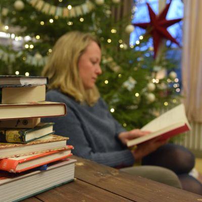 En hög med böcker. I bakgrunden en kvinna som sitter och läser.