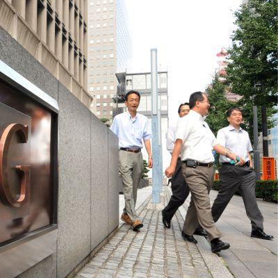 Anställda utanför AIG:s huvudkontor i Japan