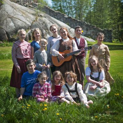 Sarah Nedergård står med en gitarr i handen och barn runt omkring sig.