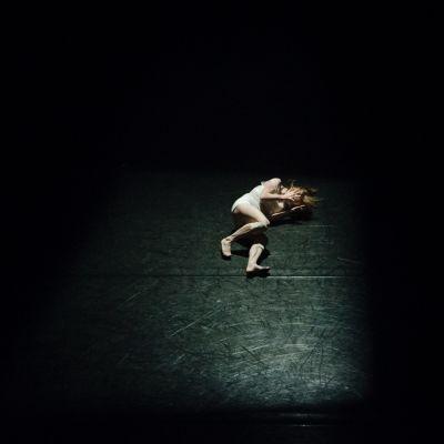Esiintyjä makaa yksin lavalla jännittyneessä asennossa kasvot peitettynä.