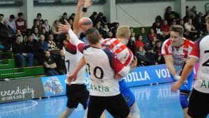 Andreas Rönnberg skjuter ett skott mellan försvararna.