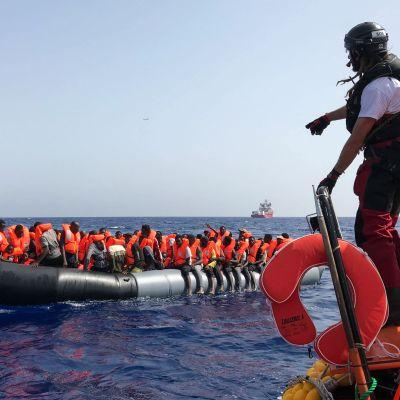 En av räddningspersonalen från fartyget Ocean Viking står på kanten av en gummibåt och förbereder sig för att rädda migranter som sitter på en annan gummibåt ute på havet.