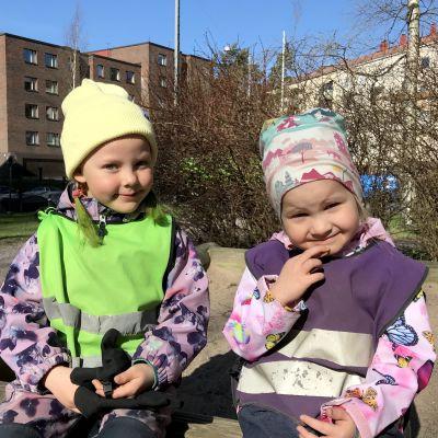 Två små flickor i jackor och mössor sitter och kisar mot solen.
