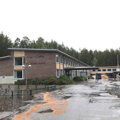 Purettava koulurakennus näyttää hylätyltä vesisateessa.
