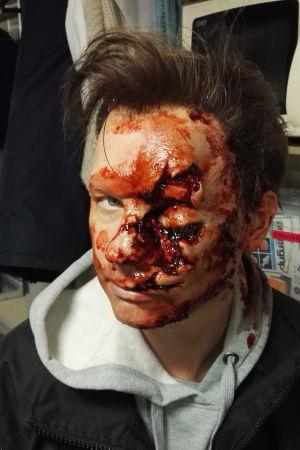 Mika Huisman katsoo kulmien alta kameraan hurjat verijäljet maskeerattuna kasvoilleen.