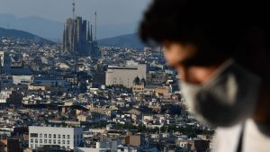 En man i ansiktsmask. I bakgrunden syns katedralen Sagrada Familia