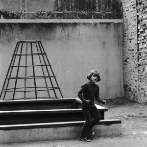 Poika ottaa askeleen Kruununhaan kivisellä pihalla, jossa hiekkalaatikko ja kivimuureja.