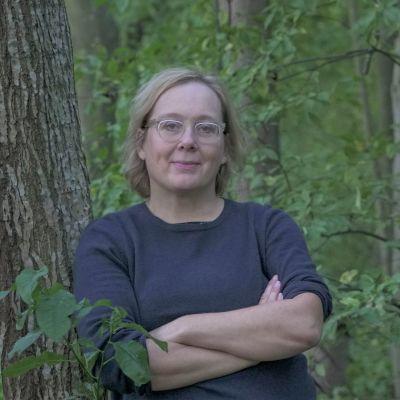 Valokuvaaja Maija Blåfield nojaa hyväntuulisena puunrunkoon kesäisessä metsikössä.