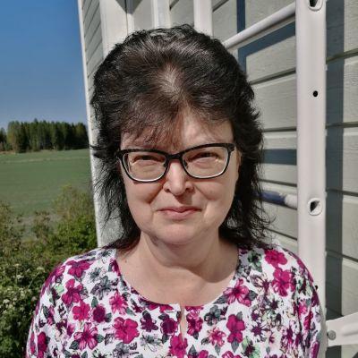 Rintakuva Marjo Torkkelista talonsa vieressä.
