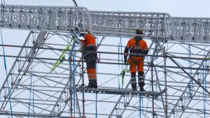 Byggarbetare uppe i byggställningar