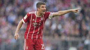 Rödklädde fotbollsspelaren Thomas Müller ropar och pekar under match.