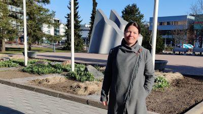 En kvinna klädd i grå, lång kappa står utomhus framför en rad flaggstänger och kisar mot kameran. Hon ler lite, har ena handen i fickan och solen skiner.