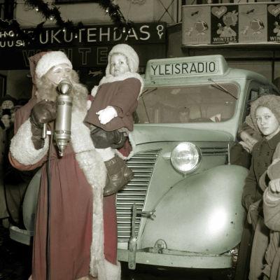 Joulupukki, jolla on sylissään pieni tyttö. Heidän takanaan on Yleisradion auto. Valokuvaa sävytetty Elävän arkiston toimituksessa.