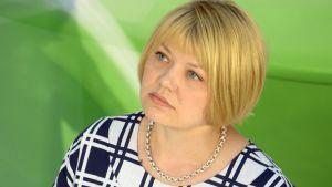 En bild på Elina Moisio - hon sitter ner och bakgrunden är grön.
