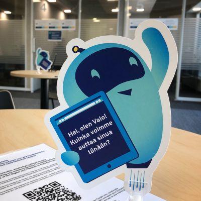 En liten robotaktig figur av papp på ett bord, med fråga om hur hen kan hjälpa kunder vid Myndigheten  för digitalisering och befolkningsdata.