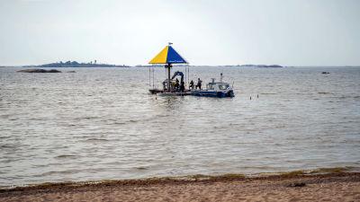 Flera personer jobbar på en vattenkarusell i havet.