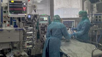 Två läkare i skyddskläder står lutade över en sjukhussäng. I salen finns mycket medicinska maskiner.