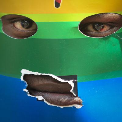 En svart man bär en mask som ser ut som en regnbågsflagga