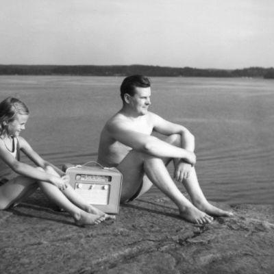 Mies ja lapsi kuuntelevat radiota rantakalliolla, mustavalkoisessa valokuvassa.