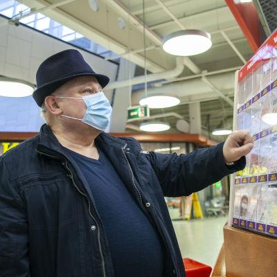 Veli Kärnä, katsomassa kaupassa lottoarpoja  Kuopiossa