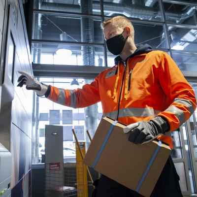kuljettaja Janne Viljala laittaa lähetyksiä pakettiautomaattiin Pitkälahden ABC -asemalla Kuopiossa