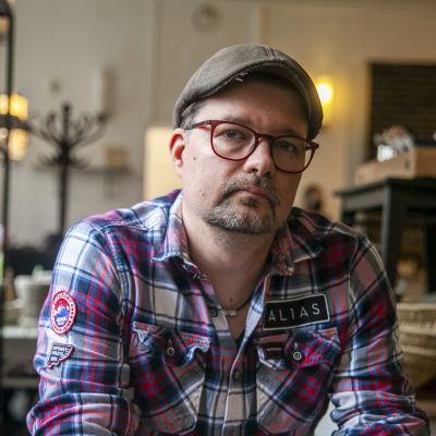 Antti Karppinen, valokuvaaja, istumassa Kuopion junaasemalla olevassa kahviossa