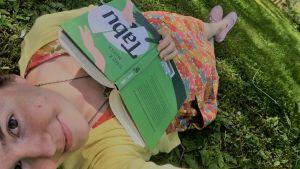 Matkalla Mikä-Mikä-Maahan -blogin Anna makaa nurmikolla ja lukee Timo K. Mukan Tabua