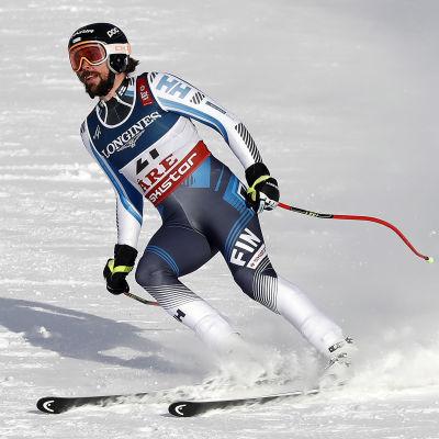 Alpintåkaren Andreas Romar bromsar med skidorna efter målgång.