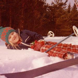 Talvisessa maisemassa nuori tyttö on kaatunut lumihankeen sukset jalassa.