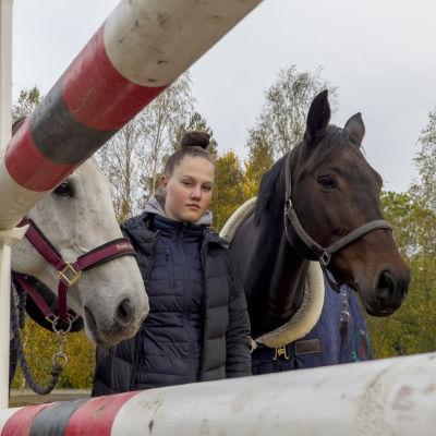 En ung kvinna med två hästar. de står bakom ett hinder som används vid banhoppning.