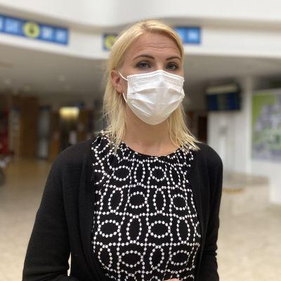 Medelålderskvinna med axellångt blont hår och munskydd tittar in i kameran.